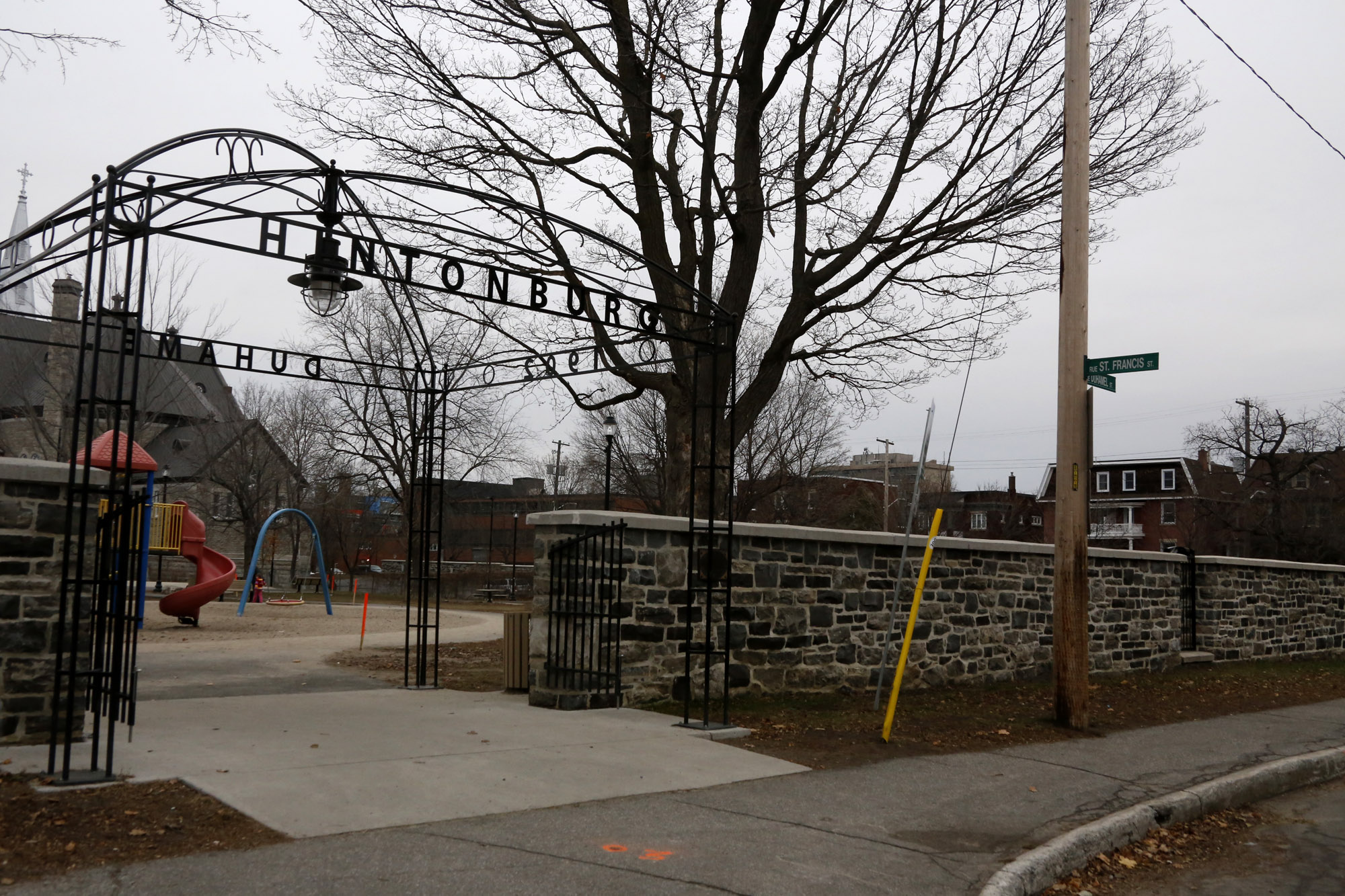 Hintonburg Park entrance, from St. Francis Street. The St. François d'Assise Church, in the background on the left, dominates the park. The wall was renovated in 2010. Photo: Stephanie Elliott 2014.